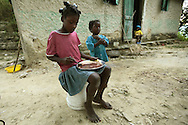 A family begins eating dinner at their home deep in the woods above Carrefour, Haiti.  The meal consist of maise (corn paste) and a bean broth over it.  It is a standard meal for the poor people living on the mountain.