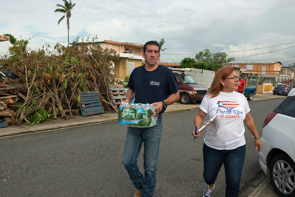 Toa Baja, PR, November 10, 2017--Jesús Pagán Torres, left, and Inamays Carreras Negrón, right, are part of a team of faculty and staff of Escuela Delia Cabán who continue to distribute water and emergency relief in Tao Baja, PR neighborhoods still without power and water 50 days after Hurricane Maria.  Escuela Delia Cabán has served as a distribution point for the Puerto Rico Recovery Fund's emergency relief efforts since it was established days after the storm hit September 20, 2017.  Photo by Lori Waselchuk/BRAF