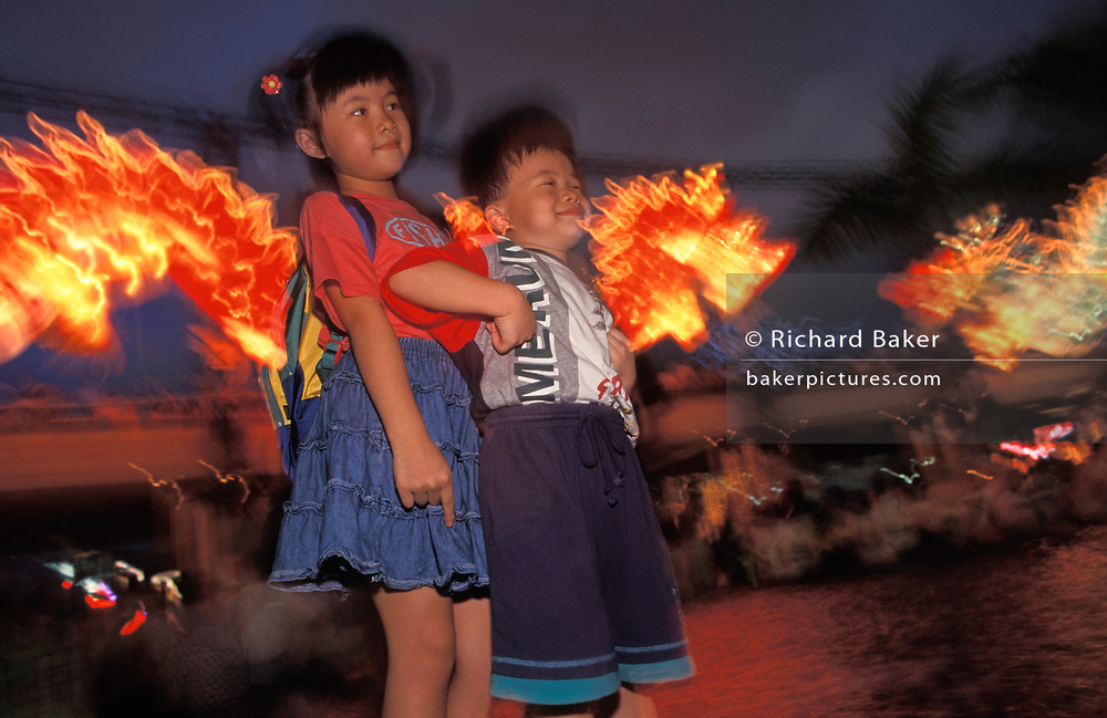 Chinese children smle during a dragon lantern party in Kowlooon, on the eve of the handover of sovereignty from Britain to China, on 30th June 1997, in Hong Kong, China. Midnight signified the end of British rule, and the transfer of legal and financial authority back to China. Hong Kong was once known as 'fragrant harbour' (or Heung Keung) because of the smell of transported sandal wood.