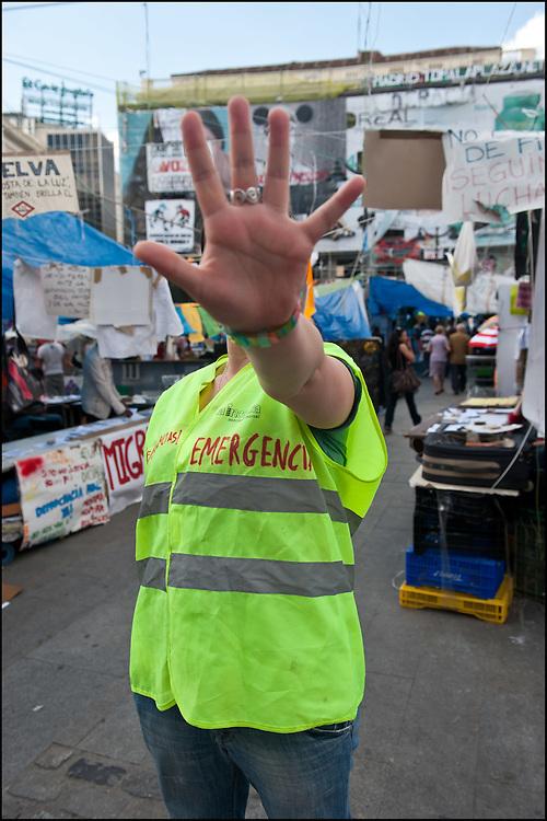 """Violetta est une infirmiere benevole sur le camp, elle ne souhaite pas etre reconnue. // Le mouvement spontane du """"15 M"""" (15 mai) compose de citoyens espagnols campe depuis 2 semaines sur la place Puerta Del Sol avec pour revendication la construction d'une democratie nouvelle. Organise en commission les citoyens prennent la parole lors d'assemblee ouverte a tous - Place Puerta Del Sol à Madrid le Juin 2011. ©Benjamin Girette/IP3Press"""