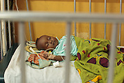 Ghana: 25 April 2012, A young child lies on a bed at the Princess Marie Louise Children's hospital in Accra. The GAVI Alliance is a public-private partnership that brings together developing country and donor governments, WHO, UNICEF, the World Bank, the vaccine industry in both industrialised and developing countries, research and technical agencies, civil society, the Bill & Melinda Gates Foundation and other private philanthropists.  Set up in 2000 as the Global Alliance for Vaccines and Immunisation, GAVI's mission is to save children's lives and protect people's health by increasing access to immunisation in the world's poorest countries.