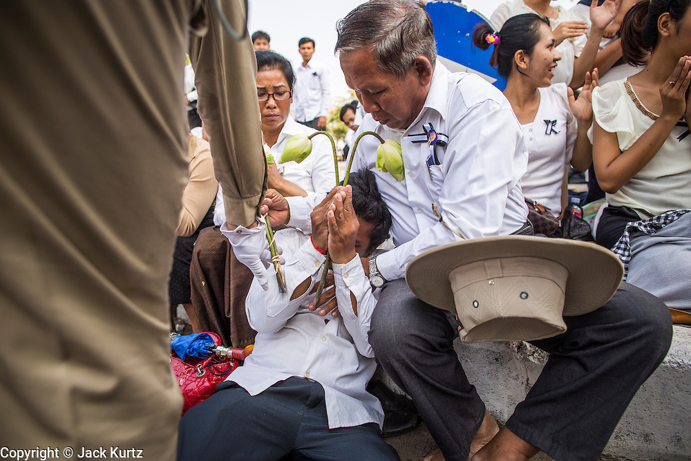 """01 FEBRUARY 2013 - PHNOM PENH, CAMBODIA: Cambodians try to help a mourner who collapsed in grief as the funeral procession of former Cambodian King Norodom Sihanouk passes him in Phnom Penh. Norodom Sihanouk (31 October 1922- 15 October 2012) was the King of Cambodia from 1941 to 1955 and again from 1993 to 2004. He was the effective ruler of Cambodia from 1953 to 1970. After his second abdication in 2004, he was given the honorific of """"The King-Father of Cambodia."""" Sihanouk died in Beijing, China, where he was receiving medical care, on Oct. 15, 2012. His cremation is will be on Feb. 4, 2013. Over a million people are expected to attend the service.    PHOTO BY JACK KURTZ"""