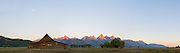 A panorama of the mormon barn at sunrise, with the peaks of the Tetons painted pink and the moon still out. Taken in Grand Teton National Park, USA.
