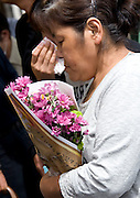 A resident carries flowers into a gym prior to being allowed briefly to return and collect valuables and other belongings from her home inside the nuclear exclusion zone in Okuma, Fukushima Prefecture, Japan on Aug. 31 2011. With some residents losing their homes in the March 11 disasters, some decided to take flowers to leave by the gravesides of deceased family members. Robert Gilhooly Photo