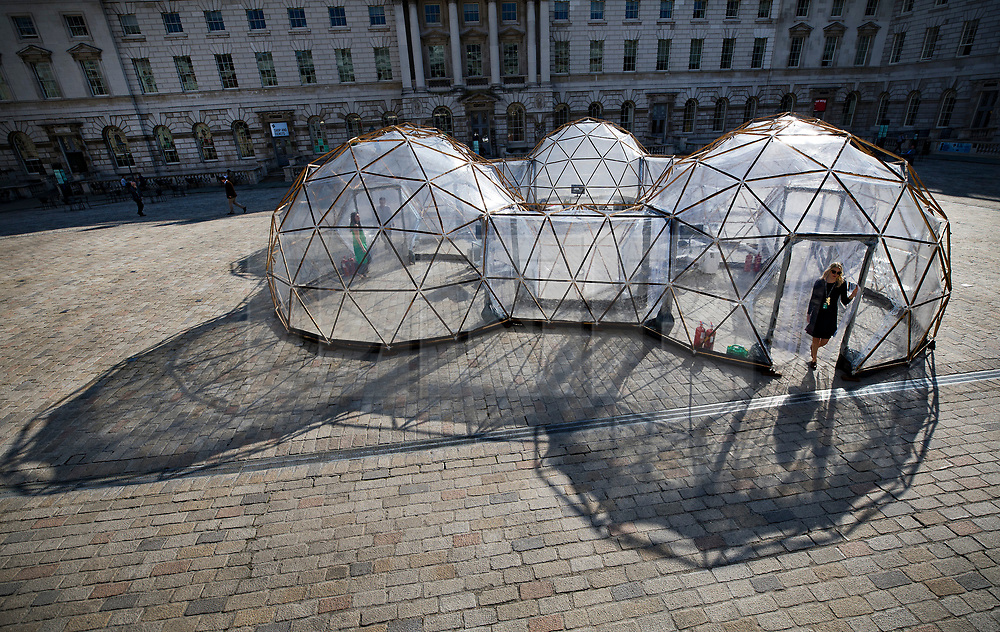 © Licensed to London News Pictures. 18/04/2018. London, UK. Visitors walk through British artist Michael Pinsky's Pollution Pods, a new sensory work, installed in the courtyard at Somerset House in London to mark Earth Day 2018. A series of five connecting domes recreate the pollution from London, Beijing, São Paulo, New Delhi and Tautra in Norway. Visitors are invited to experience first-hand the difference in the air quality of global environments. The Pollution Pods are open until 25th April 2018, including Earth Day on the 22nd April. Photo credit: Peter Macdiarmid/LNP