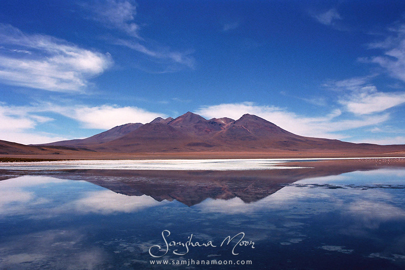 """""""So still and silent, the serenity of this place still exists fresh in my mind seven years on. Such beauty on this three day off road trip in a 4x4 across the Altiplano. Recommended to me by fellow travellers I met in La Paz. A complete surprise to be so overwhelmed with such incredible scenery, it's a whole new world up there! Bolivia is without contest, my favourite destination for mind-blowing untouched natural beauty.""""<br /> Shot on 35mm film and digitally re-mastered for optimum effect. Some analogue film texture can be seen in print which adds to the beauty of the image.<br /> Elevated 4,151m  (13,619 ft) A saline lake populated with flamingos and surrounded by huge mountains."""