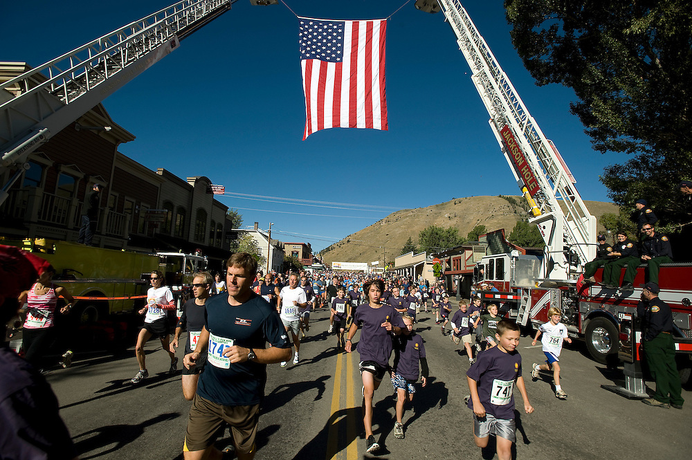 PRICE CHAMBERS / NEWS&GUIDE.Competitors gain speed as they start Old Bill's Fun Run for Charity on Saturday. Jackson Hole Fire/EMS hung the large American Flag above the course in honor of September 11th.