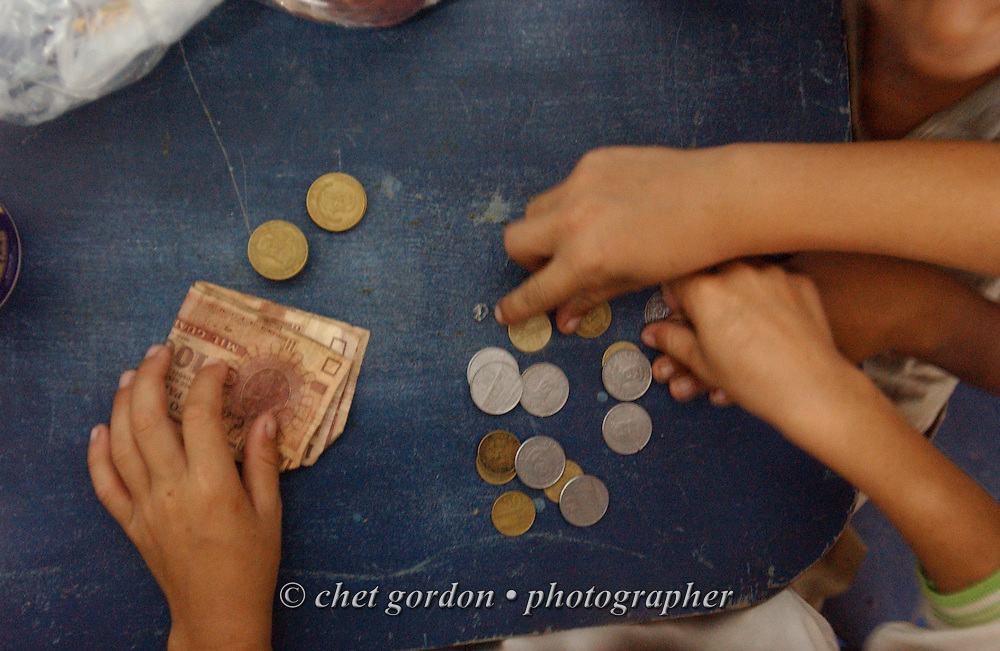 ASUNCION, PARAGUAY.  Young Paraguayan street boys count their earnings on a table in the Asociacion Cultural Justicia y Verdad (Association of Cultural Justice and Truth) in Asuncion, Paraguay on Wednesday evening, March 15, 2006. The shelter founded by Dr. Chantal Hulin, is run out of a renovated auto garage, where volunteers provide showers, administer health care, simple meals, and classroom activities to some of the hundreds of homeless street children that panhandle and clean windshields for money on the neighborhood streets.