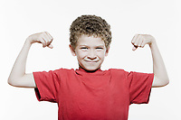 little caucasian strong boy portrait flexing muscle biceps mischief isolated studio on white background