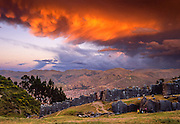 "The last orange light of sunset highlights turbulent clouds over the finely crafted Inca walls of Sacsayhuaman (Saqsaywaman), a ""Royal House of the Sun"" built on a hill above Cuzco (Cusco or Qosqo), in Peru, South America. Cuzco was the site of the historic capital of the Inca Empire from the 1200s to 1532 and was honored on the World Heritage List in 1983 by UNESCO. Francisco Pizarro officially founded Spanish Cuzco in 1534. Cuzco is the longest continuously occupied city in the Americas and is built upon the foundations of the Incas (at 3400 meters or 11,200 feet elevation). The natural light sunset was captured on Fujichrome Velvia film. Licensed by National Geographic Maps in 2008 for a Geotourism Map of Peru's Sacred Valley."