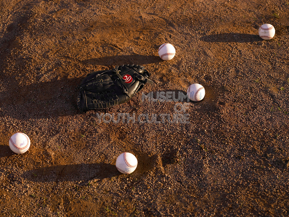 Five baseballs and a baseball glove laying on dirt.