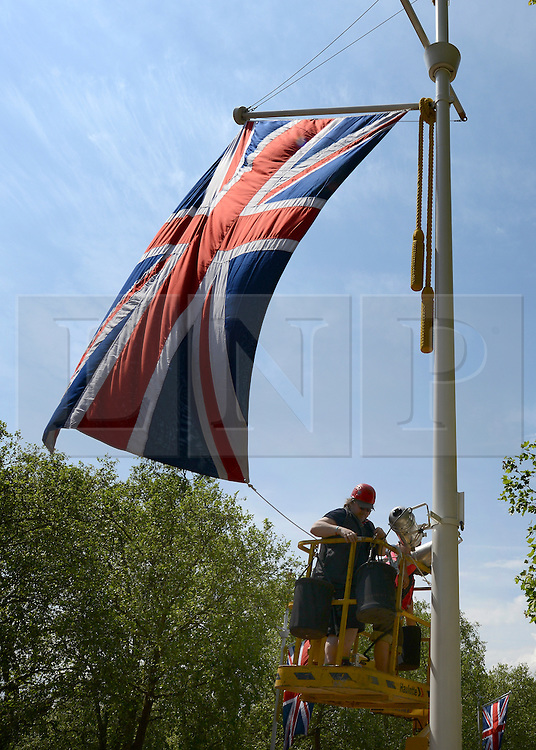 © Licensed to London News Pictures. 30/05/2012. London, UK Workmen hang lamps on a post with a Union Flag on The Mall today. A view along the Mall towards Buckingham Palace. Preparations today 20th May 2012 around London ahead of The Queen's Diamond Jubilee this weekend. Photo credit : Stephen Simpson/LNP
