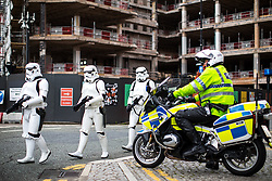 © Licensed to London News Pictures . 30/07/2017 . Manchester , UK . A garrison of Storm Troopers march by a motorbike policeman watching over the crowds at the venue . Cosplayers, families and guests at Comic Con at the Manchester Central Convention Centre . Photo credit : Joel Goodman/LNP