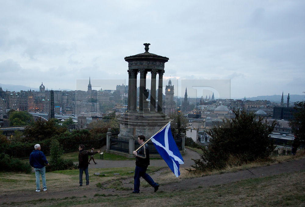 © Licensed to London News Pictures. 14/09/2014. Edinburgh, UK. A Yes campaigner walks down the top of Calton Hill with the Saltire. Photo credit: Isabel Infantes / LNP