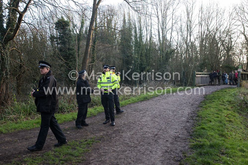 Denham, UK. 3 February, 2020. Police officers monitor and film environmental activists from Extinction Rebellion, Save Colne Valley and Stop HS2 occupying a bridge in Denham Country Park to seek to prevent works for the HS2 high-speed rail link including the felling of 200 trees and the construction of a Bailey bridge, compounds, fencing and a parking area. Part of the location for the work lies within a wetland nature reserve forming part of a Site of Metropolitan Importance for Nature Conservation (SMI). In spite of a substantial police presence, HS2 were not able to proceed with the work for the day.