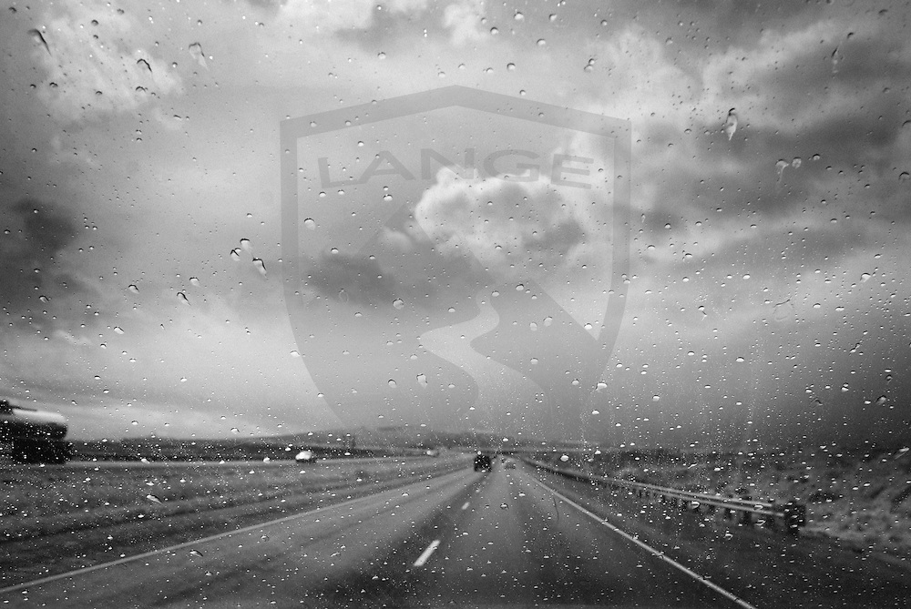 monsoon season in new mexico creates fleeting thunder and rain storms that are part of the travel experience along interstate 25 south of albuquerque.  here, rain on the windshield obscures the view of the southwest landscape.