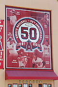 ANAHEIM - APRIL 10:  A sign featuring the Los Angeles Angels of Anaheim 50 year anniversary logo and players adorns the exterior wall of the stadium prior to the game between the Toronto Blue Jays and the Los Angeles Angels of Anaheim at Angel Stadium in Anaheim, California on Sunday April 10, 2011. The Angels won the game 3-1. (Photo by Paul Spinelli/MLB Photos via Getty Images)