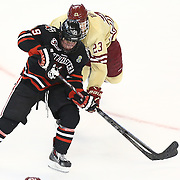 Mike Szmatula #19 of the Northeastern Huskies and Patrick Brown #23 of the Boston College Eagles fight for the puck during The Beanpot Championship Game at TD Garden on February 10, 2014 in Boston, Massachusetts. (Photo by Elan Kawesch)