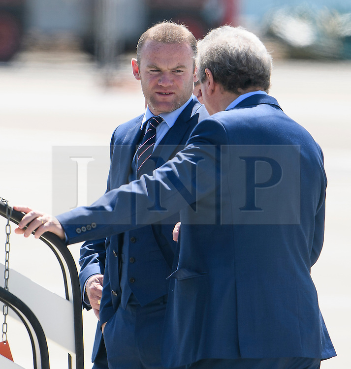 © Licensed to London News Pictures. 06/06/2016. Luton, UK. England manager ROY HODGSON and WAYNE ROONEY join other members of England national football squad as they board a plane at Luton airport in Bedfordshire, England, to head for their training camp in France, ahead of the start of the UEFA Euro 2016 championships.  Photo credit: Ben Cawthra/LNP