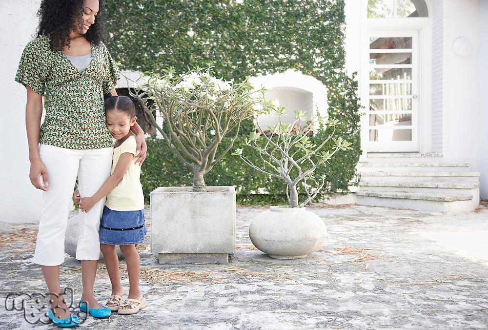 Girl (5-6 years) hugging mothers leg standing in yard