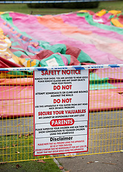 © Licensed to London News Pictures. 04/11/2018. Woking, UK. A safety notice remains on a fence surrounding the deflated slide in Woking Park after it collapsed injuring eight children. The park was holding a fireworks party when the accident happened. Photo credit: Peter Macdiarmid/LNP