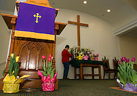 "Penny Franciosi of the ""flower committee"" starts to decorate the alter at Gilford Community Church on Friday morning for the Easter Sunday service.  (Karen Bobotas/for the Laconia Daily Sun)"