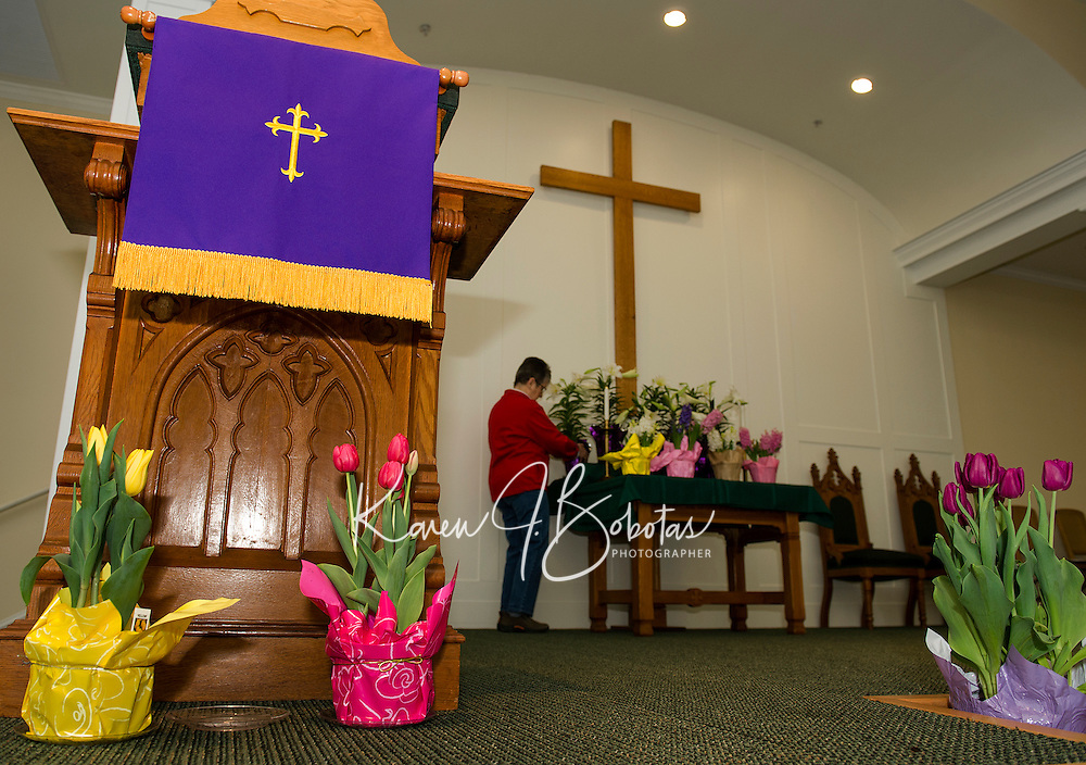 """Penny Franciosi of the """"flower committee"""" starts to decorate the alter at Gilford Community Church on Friday morning for the Easter Sunday service.  (Karen Bobotas/for the Laconia Daily Sun)"""