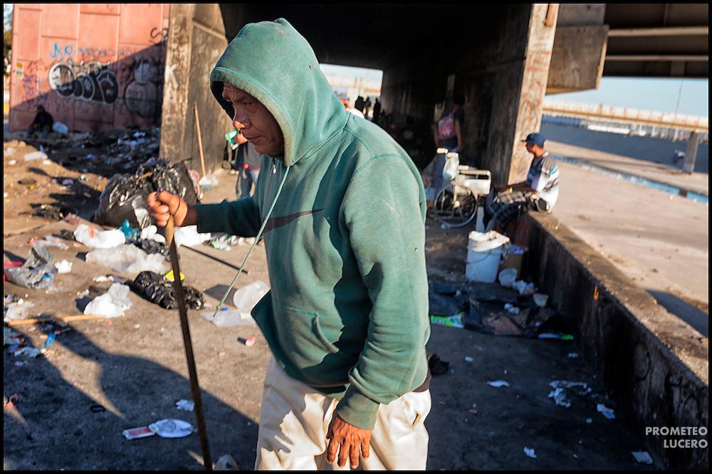 Un grupo de personas, entre ellas migrantes deportados y adictos a heroína, se reúnen bajo un puente en el Bordo de Tijuana, Baja California, el 17 de agosto de 2014. En este lugar, traficantes de drogas venden dosis de heroína o cristal, también conocido como 'crico' a precios desde 50 pesos (menos de 4 USD). (FOTO: Prometeo Lucero)