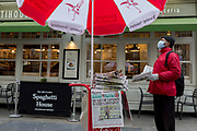 As the effects of Coronavirus continues to close down businesses and places of entertainment, and because of the governments's urge for home-working and avoidence of social gatherings, the West End of the UK's capital is unusually quieter than normal on a mid-week evening. On the day that the death toll reached 104 and that British schools would close indefinitely from the end of the week, the Evening Standard newspaper is handed out, headlining with central London being the UK's pandemic hotspot, on 18th March 2020, in London, England.