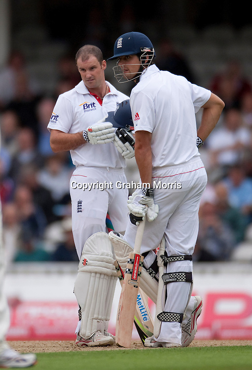 Andrew Strauss after being hit on the helmet (breaking part of the peak off) by a ball from Ishant Sharma during the fourth and final npower Test Match between England and India at the Oval, London. Opening partner, Alastair Cook, is on the right. Photo: Graham Morris (Tel: +44(0)20 8969 4192 Email: sales@cricketpix.com) 18/08/11