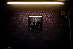 """© London News Pictures. """"Looking for Nigel"""". A body of work by photographer Mary Turner, studying UKIP leader Nigel Farage and his followers throughout the 2015 election campaign. PICTURE SHOWS - A poster of Winston Churchill adorns the purple walls of the local UKIP candidate Bill Etheridge's office in Segdley, nr Dudley, West Midlands, on April 7th 2015. Nigel Farage is seen by many UKIP supporters as being a leader akin to his Churchill and they hark back to the spirit of his days of as Prime Minister. . Photo credit: Mary Turner/LNP **PLEASE CALL TO ARRANGE FEE** **More images available on request**"""