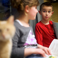 "Trey Douglas speaks with Cassandra Kraus as they read to cats up for adoption during ""The Book Buddies Program"" at the Animal Rescue League of Berks County in Birdsboro, PA on February 11, 2014.  Children in grades 1-8 read to the cats as a way to improve their reading skills and gain confidence.  The shelter animals can be a non-evaluative presence that can provide support and comfort to participants without judging them.  Students showed sustained focus and maintained a higher state of awareness, as well as improved attitudes toward school, according to researchers at Tufts University.  Photo taken February 11, 2014.  REUTERS/Mark Makela  (UNITED STATES)"
