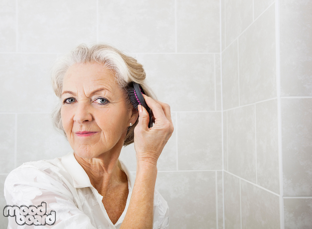 Portrait of senior woman brushing hair in bathroom