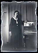 adult woman standing by a piano circa 1930s