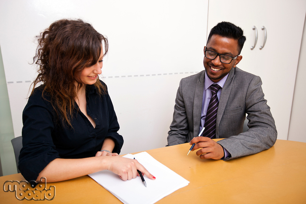 Multi-ethnic work colleagues looking at paperwork on a table