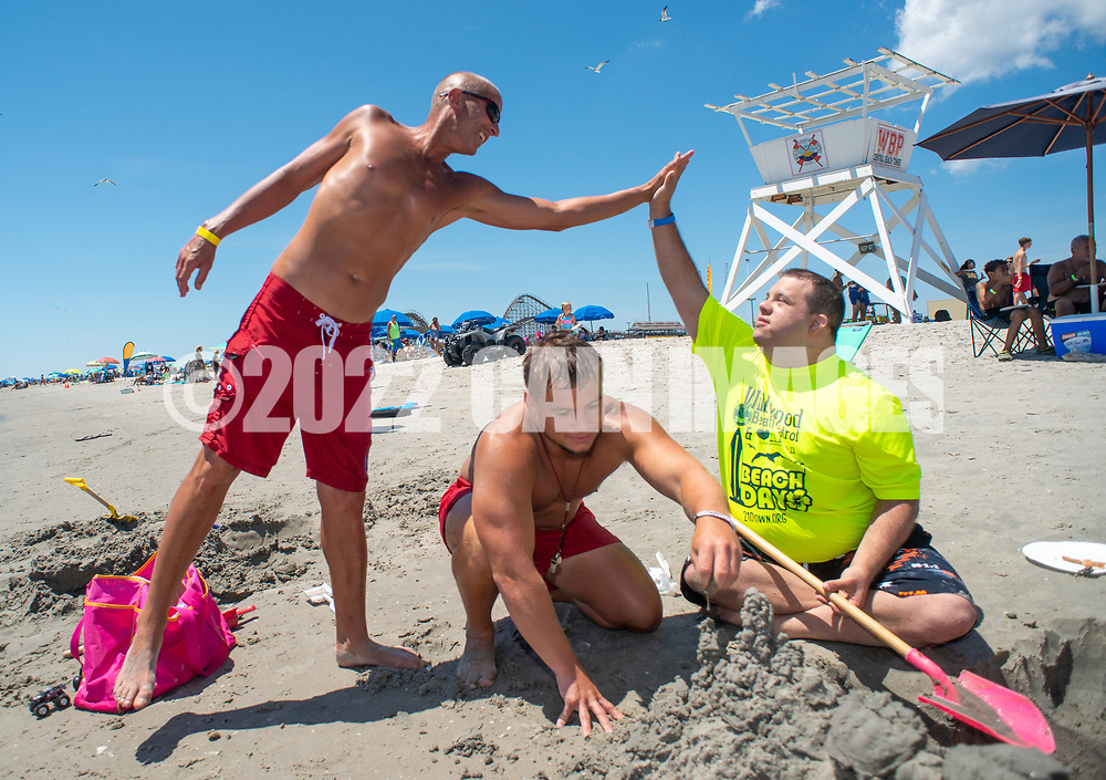 Billy Auty, Senior Career Lifeguard gives a high five to Anthony Tarquinio, 27, of Beuna, New Jersey as lifeguard Bob Endy, 22, helps dig in the sand during the 11th annual 21 Down Beach Day Monday, July 15, 2019 at Schellenger Street beach in Wildwood, New Jersey. Every summer, the Wildwood Beach Patrol opens Lincoln Ave Beach for kids with down syndrome and their families for 21 Down Beach Day. Often, kids with down syndrome aren't comfortable in the ocean. Their parents can't just relax and watch them frolic. But on July 15th, the kids swim with seasoned Wildwood lifeguards on soft-top paddle boards. (Photo by William Thomas Cain / CAIN IMAGES)