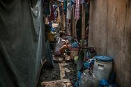 A young woman washes clothes in a narrow alleyway in Market 3 slum inside the compound of the Navotas Fish Port Complex.  The slum, which burnt to the ground in January 2017, has seen numerous extrajudicial killings.  Navotas, Metro Manila, Philippines.