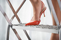 Woman wearing red high heeled shoe standing on aluminium construction close-up of foot