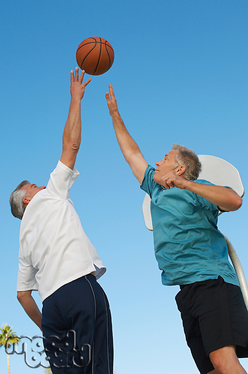Senior men playing basketball on outdoor court