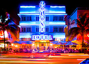 The neon-lit, Art Deco-style Colony Hotel and sidewalk cafe at night on Miami Beach's Ocean Drive in South Beach, with a  red Ferrari parked in front. The building was designed by Henry Hohauser in 1935