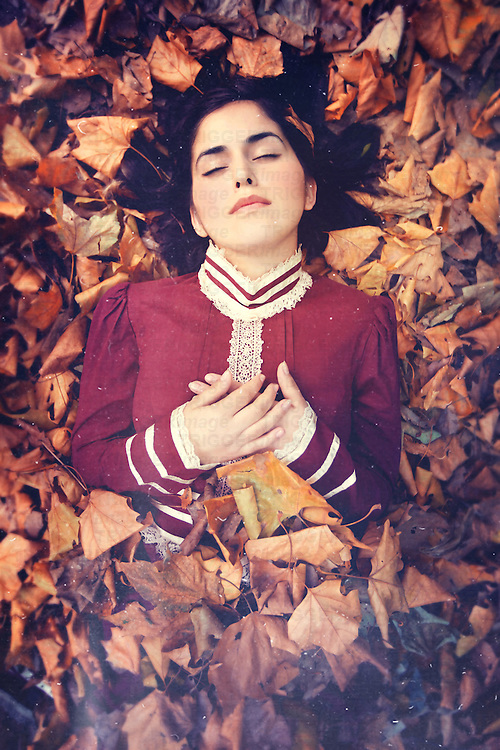 A young woman in Victorian style dress, lying on and partially covered by leaves, with her eyes closed.