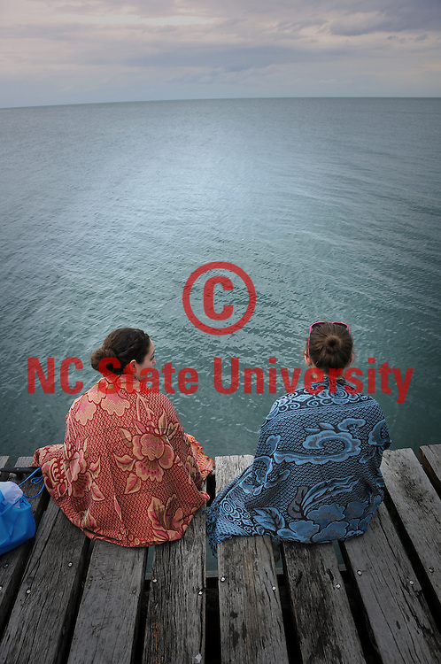 Kenzie Richards and Caitlyn Hauser (right) sit on a Punta Gorda pier and relax under their newly purchased blankets as they look out over the Caribbean.