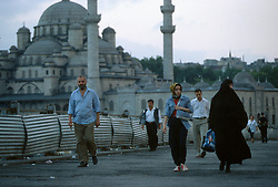TURKEY ISTANBUL JUL02 - More or less veiled women cross Galatay Bridge with the Yeni Cami, one of Istanbuls more impressive mosques...jre/Photo by Jiri Rezac..© Jiri Rezac 2002..Contact: +44 (0) 7050 110 417.Mobile:   +44 (0) 7801 337 683.Office:    +44 (0) 20 8968 9635..Email:     jiri@jirirezac.com.Web:     www.jirirezac.com
