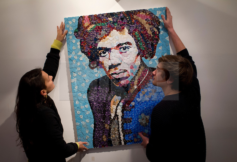 © Licensed to London News Pictures. 02/04/2013. London, UK. Staff hang a portrait of Jimi Hendrix by Manchester based mosaic artist Ed Chapman made completely from guitar plectrums in a pop-up shop set up to celebrate a new album by the late guitar legend in London today (02/04/2013). The shop, called 'People, Hell and Angels' 'located near London's Carnaby Street, runs from the 1st of April until the 12th of April 2013 and features memorabilia, music and photographs of the guitarist and singer who died in 1970 of a drug overdose. Photo credit: Matt Cetti-Roberts/LNP