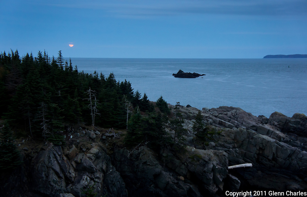A full moon rises over the Bay of Fundy with Grand Manan in the distance.  Viewed from the bold coast hiking trails in Maine.