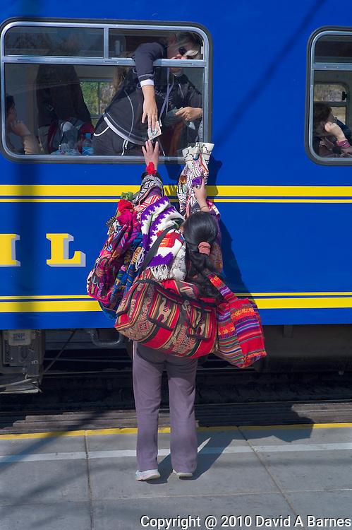 Vendor making sale thru train window, Ollantaytambo, Peru
