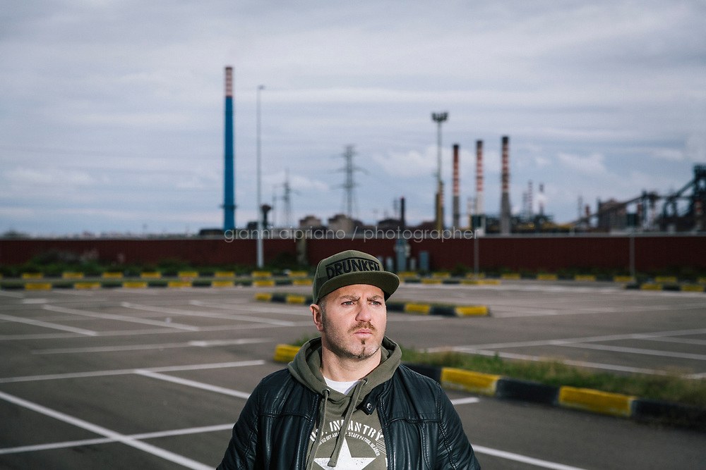 TARANTO, ITALY - 22 FEBRUARY 2018: Alessio Peretto (42), who has worked at the ILVA steel mill since 200  but is nonetheless part of activist group trying to shut it down, poses for a portrait in fron the plant in Taranto, Italy, on February 22nd 2018.<br /> <br /> Taranto, a  formerly lovely town on the Ionian Sea has for the last several decades been dominated by the ILVA steel mill, the largest steel plant in Europe. It was built by the government in the 1960s as a means of delivering jobs to the economically depressed south, but has been implicated for a cancer as dioxin and mercury have seeped into local groundwater, tainting the food supply, while poisoning the bay and its once-lucrative mussels.