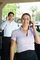 Business couple using mobile phones outdoors