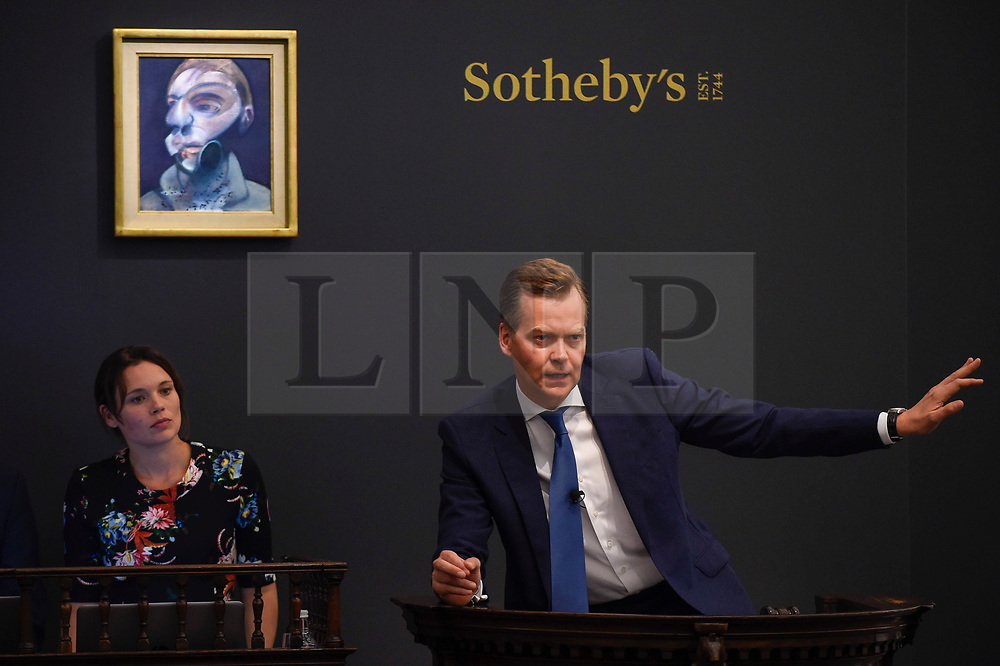 © Licensed to London News Pictures. 26/06/2019. LONDON, UK. Oliver Barker, Chairman, Sotheby's Europe, fields bids for ''Self-Portrait'' by Francis Bacon, (Est. £15,000,000 - 20,000,000) which sold for a hammer price of £14,350,000 at Sotheby's Contemporary Art Evening Sale in their New Bond Street galleries.  Photo credit: Stephen Chung/LNP