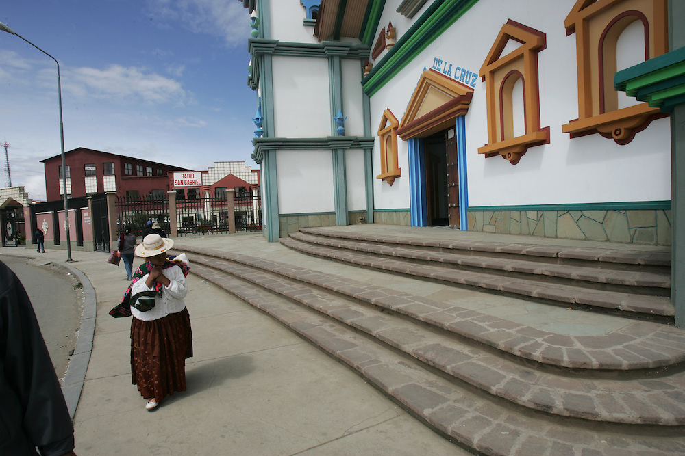 """A woman walks in front of a church that Father Sebastian Obermaier built in El Alto, Bolivia. a town he has lived in for 27 years .  """"I don't feel Bolivian, I feel Aymara"""" he says, referring to the Aymara indigenous population that makes up more than 80% of El Alto. Father Obermaier has been designing and building churches in El Alto for the past 10 years, with a goal of building one church for every 10,000 inhabitants of the city, which currently has nearly 700,000 people living in it.  Everyone that visits Bolivia can see his numerous churches from the window of their airplane as it lands in El Alto.  The churches are marked by a style unique to Father Obermaier, that mixes indigenous symbols with tall towers and bright colors, that leave every church looking different, as if they were straight out of a children's pop-up book."""